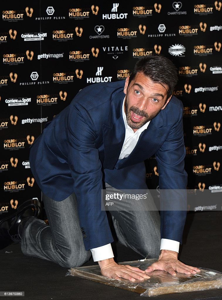 Italian goal keeper Gianluigi Buffon leaves a permanent mould of his footprints on 'The Champions Promenade', on the seafront of the Principality of Monaco, on October 11, 2016 in Monaco. / AFP / Yann COATSALIOU