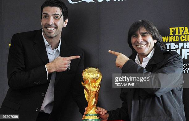 Italian goalkeeper and 2006 world champion Gianluigi Buffon jokes with 1982 world champion Bruno Conti as they pose next to the World Cup trophy at...