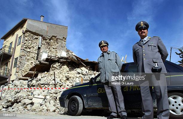 Italian 'Guardia di Finanza' police officers guard a site of a building collapse November 2 2002 in the town of San Giuliano di Pugia which is...