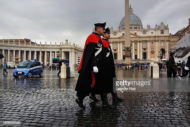 Italian guards walk in St Peter's Square as poeple wait for smoke to emanate from the chimney on the roof of the Sistine Chapel which will indicate...
