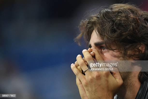 Italian high jumper Gianmarco Tamberi cries as the wathces the athletics at the Rio 2016 Olympic Games at the Olympic Stadium in Rio de Janeiro on...
