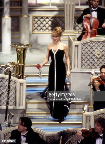 Italian host Lorella Cuccarini with an evening gown and a red rose on the stairs in the middle of the orchestra during XLIII Sanremo Italian Song...