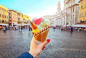 Italian ice - cream cone held in hand on the background of Piazza Navona in Rome , Italy