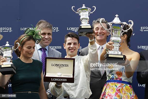 Italian jockey Cristian Demuro poses with his trophy after coming in first on La Cressonniere during the 167th 'Prix de Diane' a 2100metre flat horse...