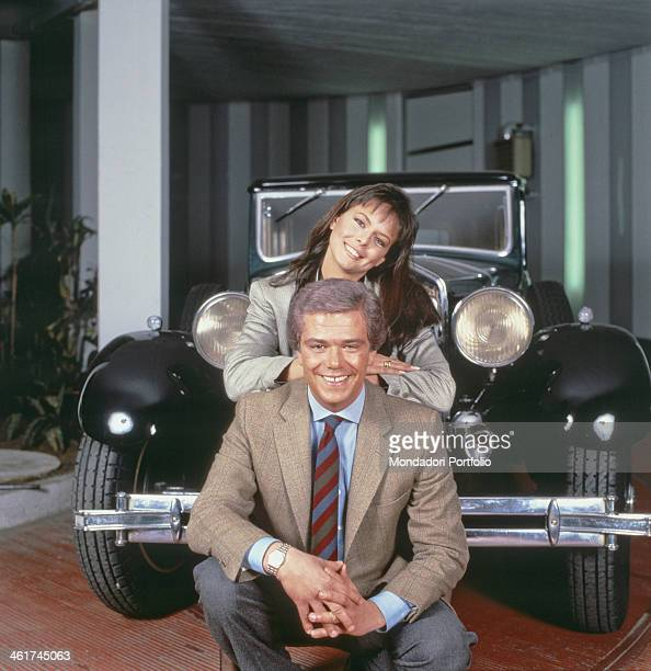 Italian journalist and presenter Cesare Cadeo and Italian presenter Paola Perego posing smiling in front of a car of the American automotive company...
