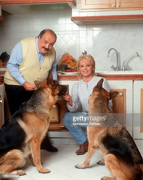 Italian journalist and TV host Maurizio Costanzo feeding two German Shepherds in the kitchen beside his wife and Italian TV presenter Maria De...