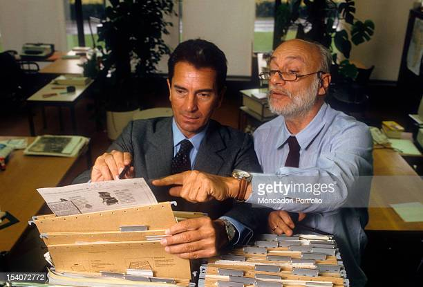 Italian journalist Carlo Rossella looking at a filing cabinet with another man 1980s