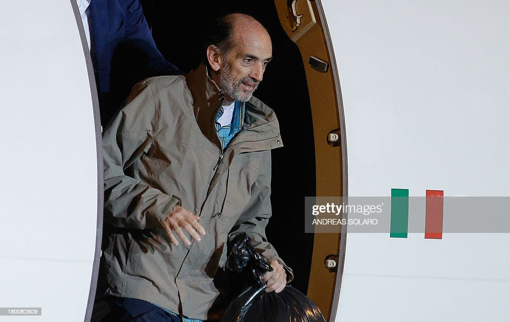 Italian journalist Domenico Quirico and Belgian national Pierre Piccinin (unseen), both kidnapped in Syria in early April, disembark from the airplane on September 9, 2013 at Ciampino military airport in Rome.