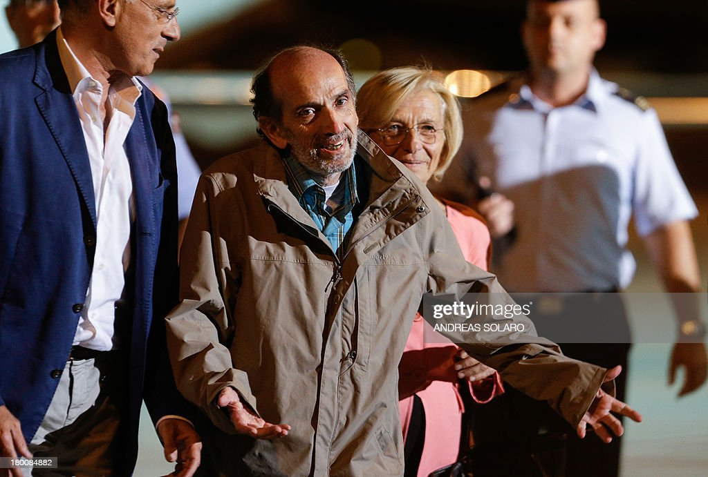 Italian journalist Domenico Quirico (C) gestures to journalists, who kidnapped in Syria in early April, after disembark from the airplane on September 9, 2013 at Ciampino military airport in Rome. AFP PHOTO / ANDREAS SOLARO