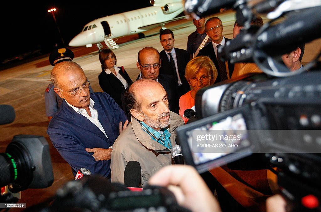 Italian journalist Domenico Quirico (C), who was both kidnapped in Syria in early April, answers to journalists after disembark from the airplane on September 9, 2013 at Ciampino military airport in Rome.