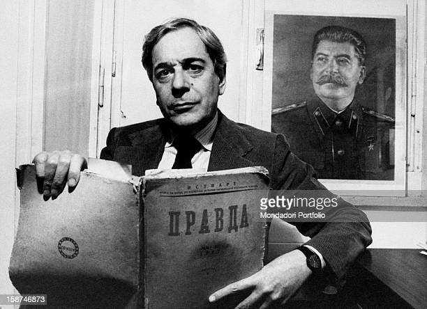Italian journalist Enzo Bettiza showing a collection of issues of the Soviet newspaper Pravda Behind him a portrait of Soviet politician Stalin 1980s