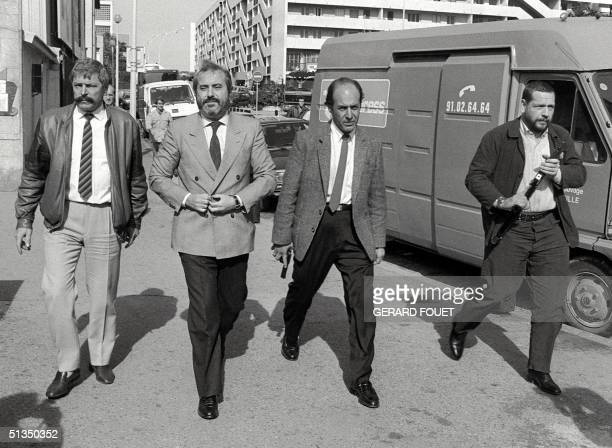 Italian Judge Giovanni Falcone surrounded by armed bodyguards arrives 21 October 1986 in Marseille to meet his French counterparts in charge to...