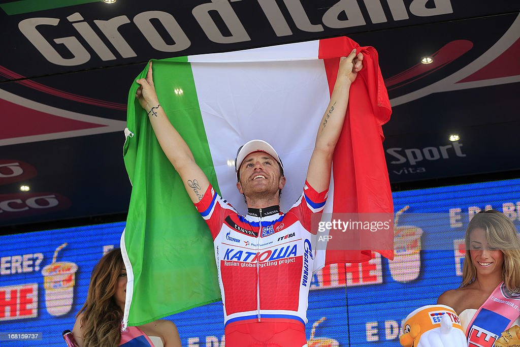 Italian Luca Paolini celebrates on the podium of the third stage of 96th Giro d'Italia going from Sorrento to Marina di Ascea on May 6, 2013 in Marina di Ascea. Luca Paolini won the third stage of the Giro d'Italia to take the overall leader's pink jersey following the 222km ride from Sorrento to Marina di Ascea with Tour de France winner Cadel Evans taking the second place and Giro champion Ryder Hesjedal finishing third.