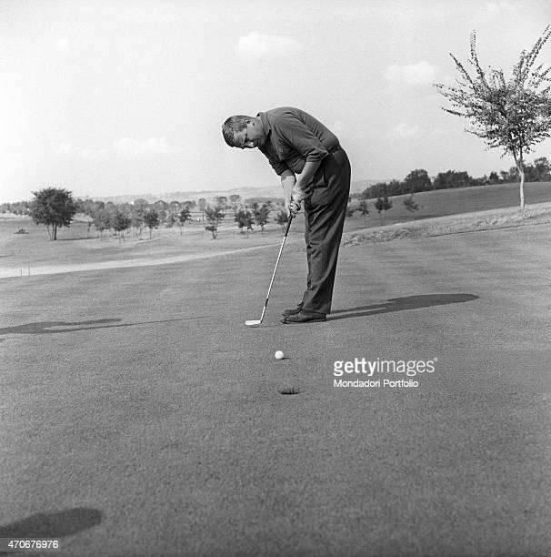'Italian manager and amateur golf player Alberto Schiaffino doing a putt to send the ball into the hole by this stroke The golf player is a member of...