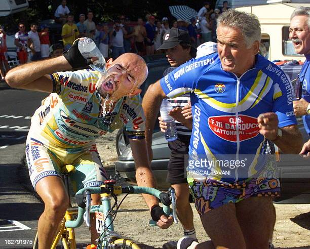 Italian Marco Pantani sprays water on his face as he is supported by a spectator in the Plateau de Beille climb during the 11th stage of the Tour de...
