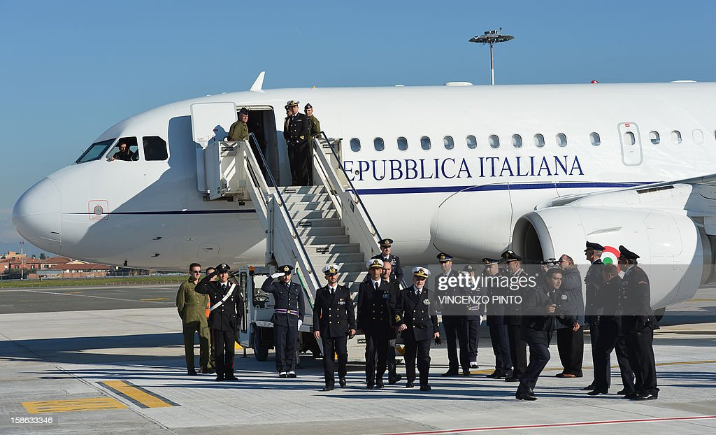Italian marines Massimiliano Latorre (C) and Salvatore Girone (L) arrive with Admiral Luigi Binelli Mantelli (R) at Ciampino airport near Rome, on December 22, 2012.An Indian court allowed two Italian marines awaiting trial for shooting two fishermen to go home for Christmas, despite prosecution fears that they will not return. The marines shot dead the fishermen off India's southwestern coast near the port city of Kochi in February while guarding an Italian oil tanker, but they deny murder on the grounds that they mistook their victims for pirates.