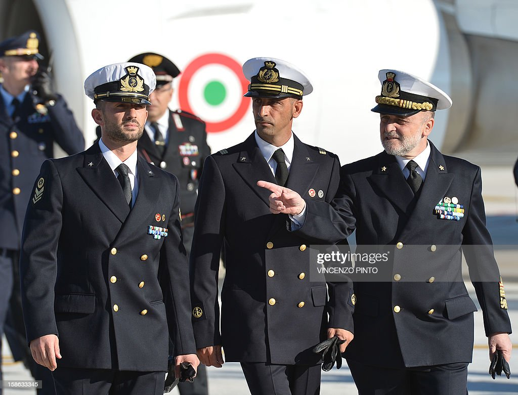 Italian marines Massimiliano Latorre (C) and Salvatore Girone (L) arrives together with Admiral Luigi Binelli Mantelli (R) arrive at Ciampino airport near Rome, on December 22, 2012.An Indian court allowed two Italian marines awaiting trial for shooting two fishermen to go home for Christmas, despite prosecution fears that they will not return. The marines shot dead the fishermen off India's southwestern coast near the port city of Kochi in February while guarding an Italian oil tanker, but they deny murder on the grounds that they mistook their victims for pirates.