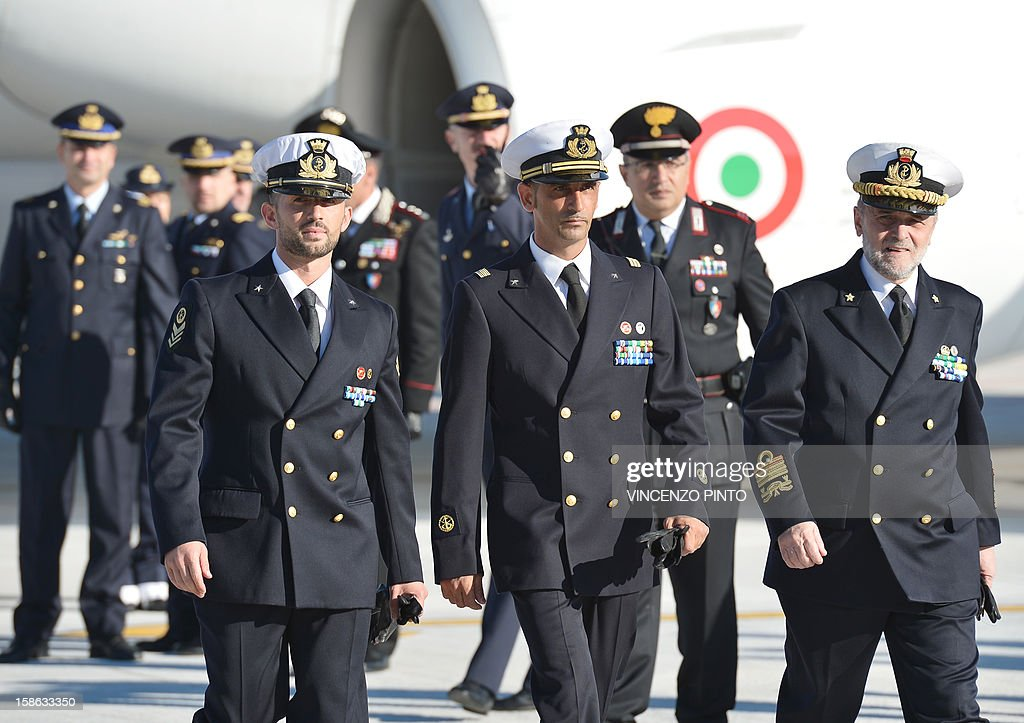 Italian marines Massimiliano Latorre (C) and Salvatore Girone (L) walk with Admiral Luigi Binelli Mantelli (R) arrive at Ciampino airport near Rome, on December 22, 2012.An Indian court allowed two Italian marines awaiting trial for shooting two fishermen to go home for Christmas, despite prosecution fears that they will not return. The marines shot dead the fishermen off India's southwestern coast near the port city of Kochi in February while guarding an Italian oil tanker, but they deny murder on the grounds that they mistook their victims for pirates.