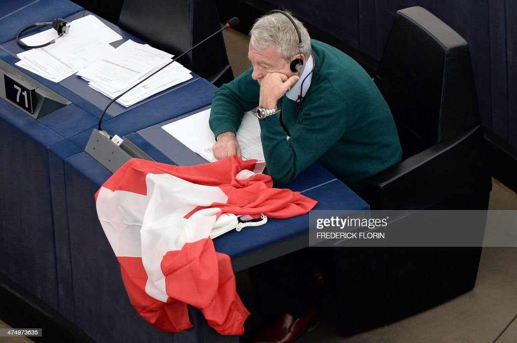 Italian member of the European parliament Francesco Enrico Speroni holds a Swiss flag as he attends a debate on EU-Switzerland relations in Strasbourg, eastern France, on February 26, 2014. AFP PHOTO / FREDERICK FLORIN