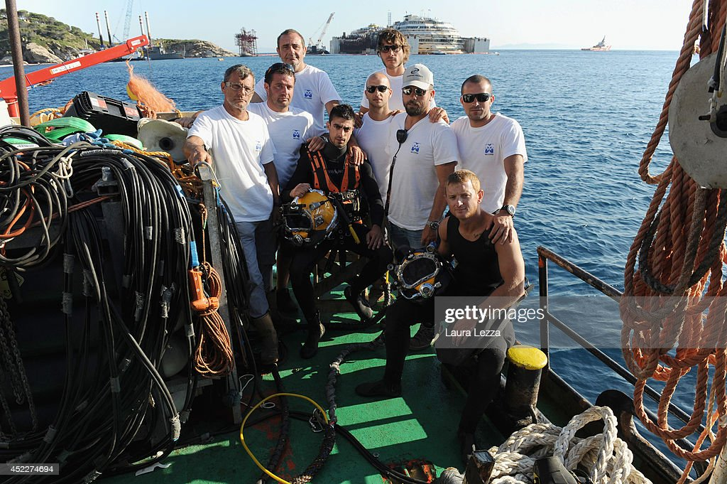 Italian Micoperi divers pose on a tug boat following the first stage of refloating operations on July 17, 2014 in Isola del Giglio, Italy. The wreck has been refloated and will be towed to the port of Genoa for dismantling.