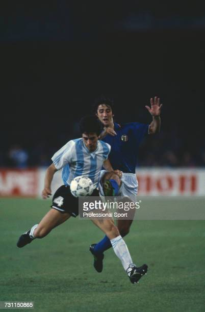 Italian midfielder Fernando De Napoli attempts to tackle Argentine player Jose Basualdo for the ball during the semi final match between Argentina...