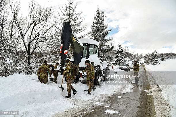 Italian military soldiers clear out the snow next to a bulldozer on the main road to Amatrice after an earthquake struck the region on January 19...