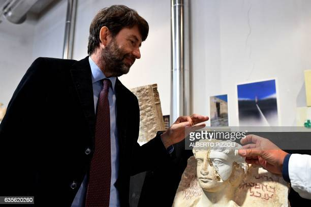 Italian Minister for Cultural Heritage Activities and Tourism Dario Franceschini looks at a restorer fixing a restored piece of the face of a man...