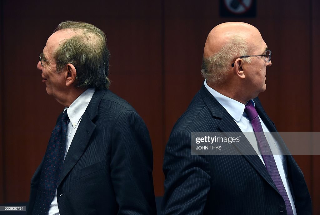 Italian Minister of Economy and Finance Pier Carlo Padoan (L) and France's Minister of Finance and Public Accounts Michel Sapin (R) look on during a Eurogroup meeting at the European Union headquarters in Brussels on May 24, 2016. Eurozone finance ministers said they hoped to unlock vital bailout cash for Greece on May 24, but warned of tough talks on debt relief that the IMF has demanded as the price for staying with the programme. / AFP / JOHN