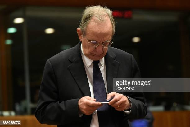 Italian Minister of Economy and Finance Pier Carlo Padoan looks at his mobile phone prior to a session of the Economic and Financial Affairs Council...