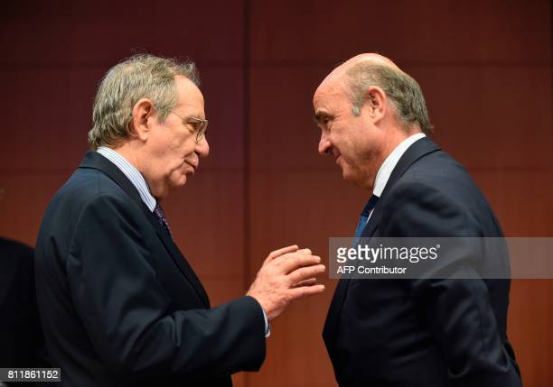 Italian Minister of Economy and Finance Pier Carlo Padoan speaks with Spain's Economy Minister Luis de Guindos during a Eurogroup meeting on July 10...