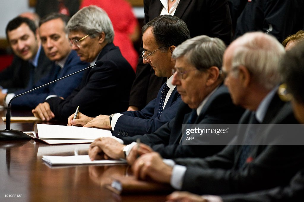 Italian minister of Foreign Affairs Franco Frattini (C) signs documents during a meeting with Venezuelan President Hugo Chavez (out of frame) in Caracas on May 27, 2010. AFP PHOTO/Miguel GUTIERREZ