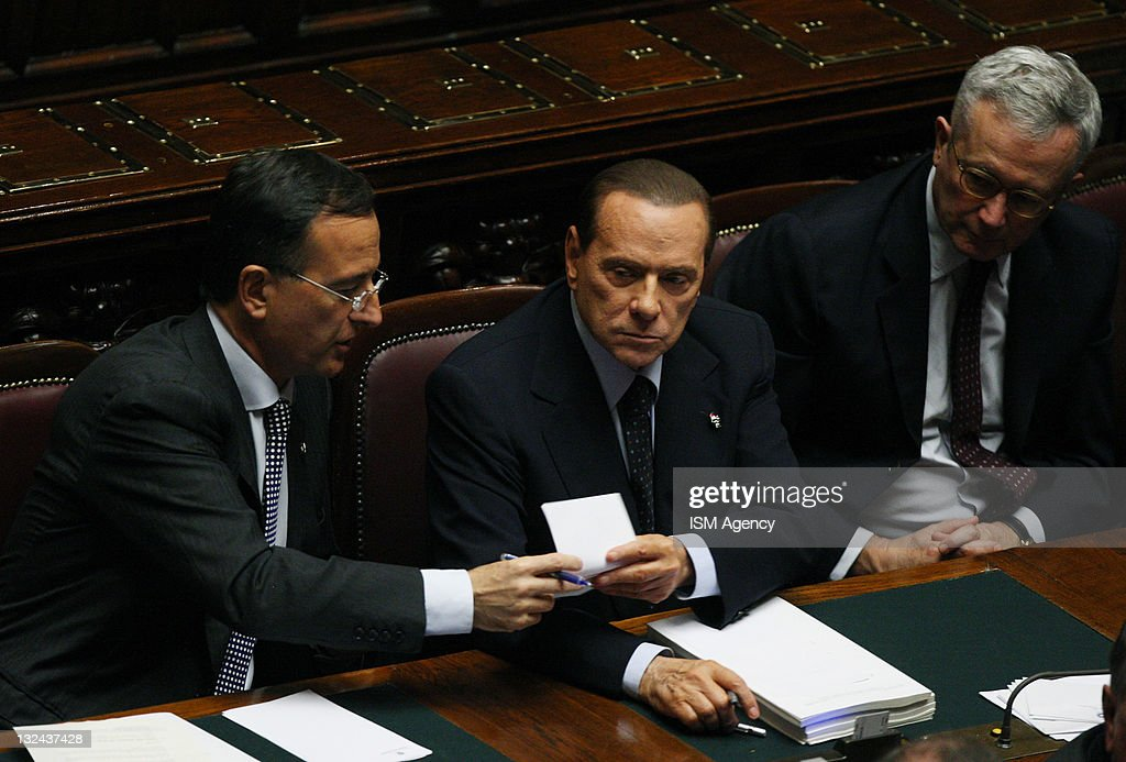 Italian Minister of Foreign <a gi-track='captionPersonalityLinkClicked' href=/galleries/search?phrase=Franco+Frattini&family=editorial&specificpeople=536993 ng-click='$event.stopPropagation()'>Franco Frattini</a> and Italian Prime Minister <a gi-track='captionPersonalityLinkClicked' href=/galleries/search?phrase=Silvio+Berlusconi&family=editorial&specificpeople=201842 ng-click='$event.stopPropagation()'>Silvio Berlusconi</a> pass a piece of paper as Italian Finance Minister <a gi-track='captionPersonalityLinkClicked' href=/galleries/search?phrase=Giulio+Tremonti&family=editorial&specificpeople=234567 ng-click='$event.stopPropagation()'>Giulio Tremonti</a> looks on during a vote on 2012 budget law on November 12, 2011 in Rome, Italy. Italian Prime Minister <a gi-track='captionPersonalityLinkClicked' href=/galleries/search?phrase=Silvio+Berlusconi&family=editorial&specificpeople=201842 ng-click='$event.stopPropagation()'>Silvio Berlusconi</a> has agreed to resign after Tuesday's vote on the 2012 budget, where he managed to muster only 308 of the 630 votes in the lower house of parliament, which is expected to allow his government to be replaced by a technical government lead by Mario Monti. Pressure is mounting amidst fears that Italy could become the next victim of the Euro-zone debt crisis with the government's borrowing costs rising to a new record of 6.74% on Tuesday.