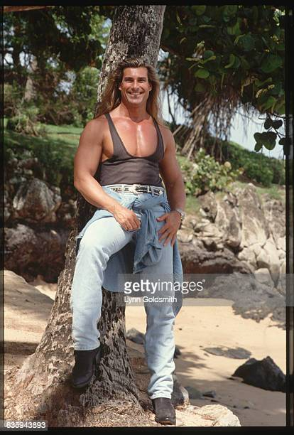 Italian model Fabio wears a tank top and jeans while leaning against a tree in Hawaii