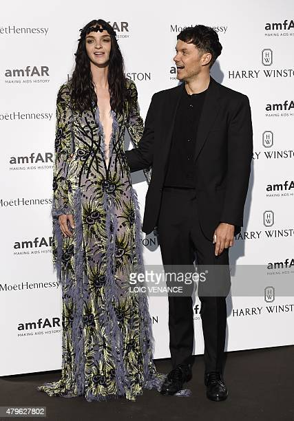 Italian model Mariacarla Boscono and Danish fashion stylist Jacob K pose as they arrive for the amfAR dinner on the sidelines of the Paris fashion...