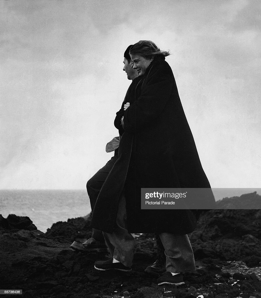 Italian motion picture director Roberto Rossellini and his second wife Swedish actress Ingrid Bergman stand on the rugged windswept shore of an...
