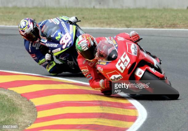 Italian Moto GP rider Loris Capirossi takes a corner ahead of compatriot Marco Melandri during the Italian Grand Prix at Mugello's circuit 05 June...