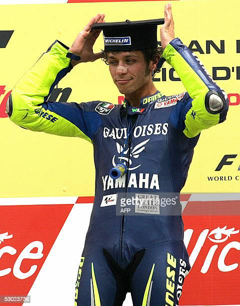 Italian Moto GP rider Valentino Rossi adjusts his graduation cap making a joke of the fact that he recently received an honorary degree from the...