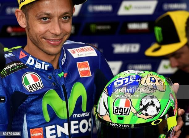 Italian Movistar Yamaha rider Valentino Rossi presents his new helmet dedicated to AS Roma football star Francesco Totti and late moto racer Nicky...