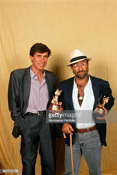Italian musician and singersongwriter Lucio Dalla and Italian singer and TV presenter Gianni Morandi showing the Telegatto award that they won for...