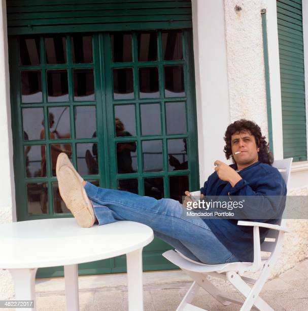 Italian musician and singersongwriter Pino Daniele smoking a cigarette sitting on a chair leaning his legs on the table July 1987