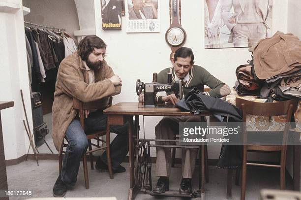 Italian musician singersongwriter and writer Francesco Guccini watching Italian tailor Nino Nativi sewing a pair of trousers Pavana 1980