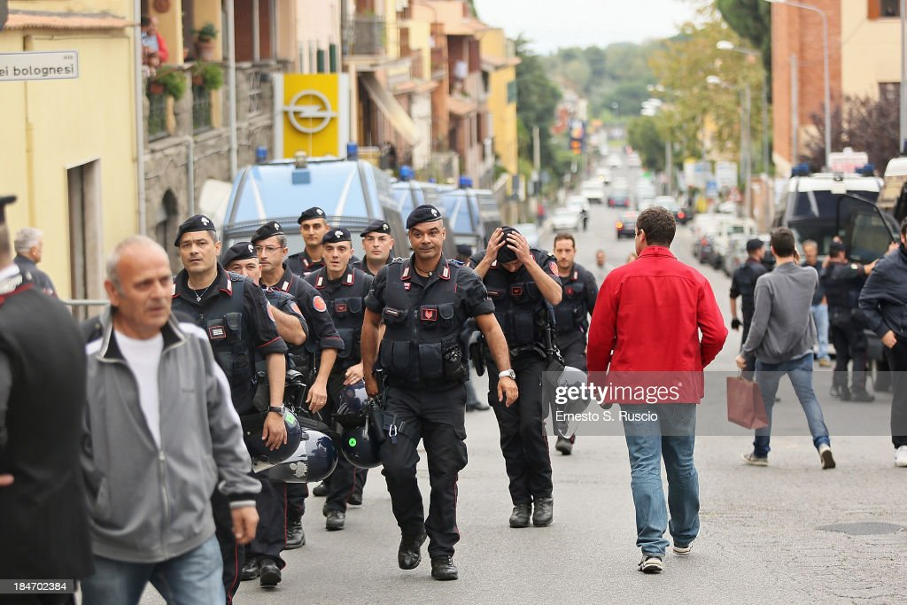 Italian officials arrive to the church of Lefebvriani where people have been protesting on October 15, 2013 in Albano Laziale, Italy. The funeral of Erich Priebke, a former SS officer convicted of participating in the massacre of 335 citizens in Italy during World War II will now take place at the Lefebvriani Chapel in Albano Laziale, after the Catholic Church announced in a statement soon after his death that 'no public funeral would be granted to him in the city or outskirts of Rome'. His burial is not yet settled after his German hometown refused to allow his burial there.