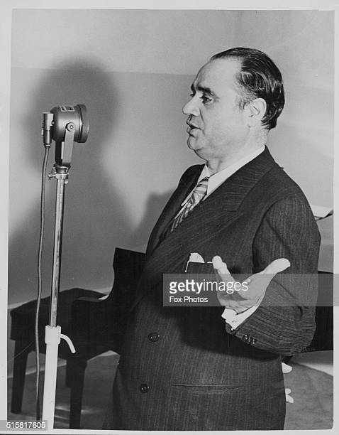 Italian opera tenor Beniamino Gigli singing into a microphone in a recording studio during a visit to HMV's new West End showroom London circa 1940