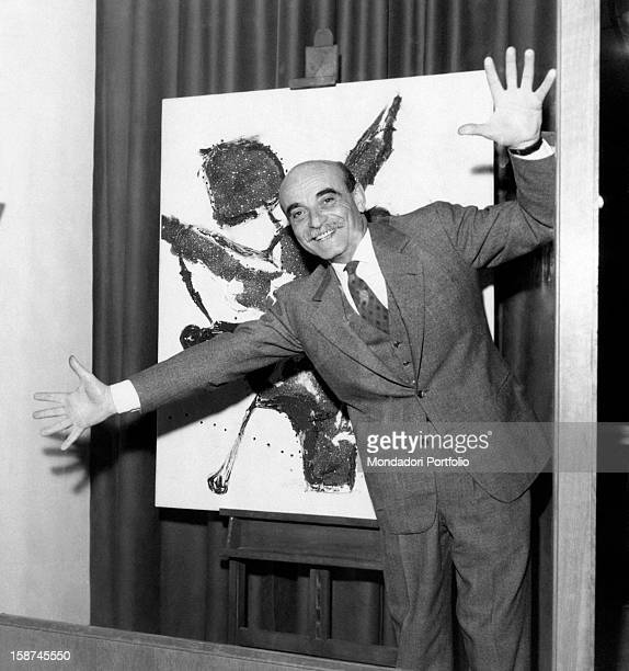 Italian painter and sculptor Lucio Fontana joking in front of a painting at the Galleria del Naviglio milan 1950s