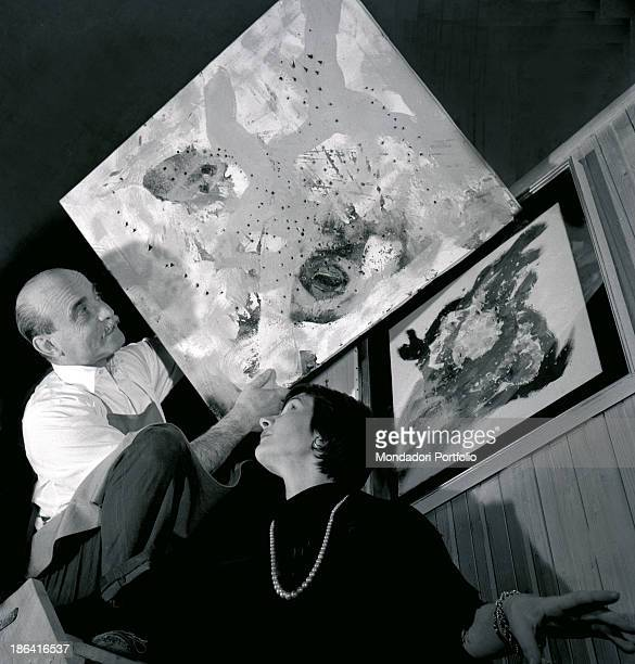 Italian painter ceramist and sculptor Lucio Fontana showing his Concetto spaziale kept at his atelier in Corso Monforte Milan Milan April 1955