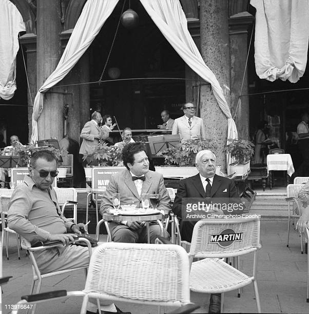 Italian painter Giorgio De Chirico having a drink in SMark Square with poet Mario Stefani sitting at a cafe terrace with an orchestra behind them...