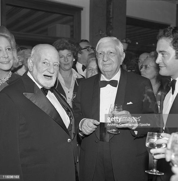 Italian painter Giorgio De Chirico standing with a glass of wine in his hand next to Rene Cassin Peace Nobel Prize in 1968 both wearing a tuxedo and...