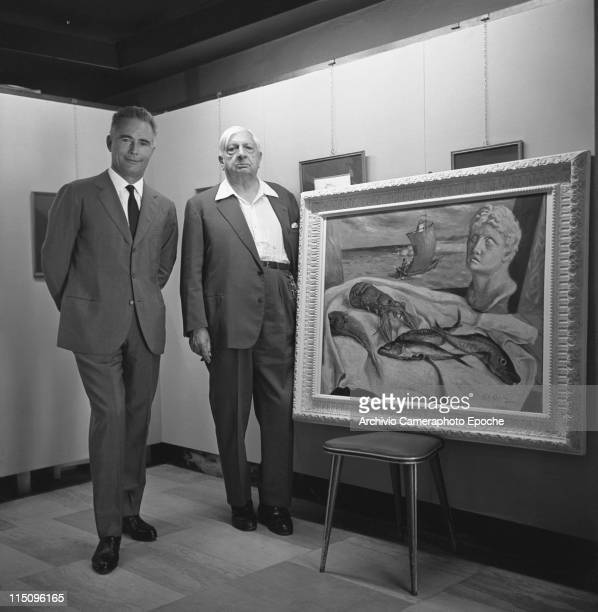 Italian painter Giorgio De Chirico wearing a dark suit standing with a man next to one of his paintings representing a seashore with a boat and some...