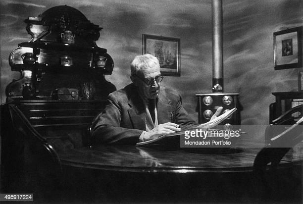 Italian painter Giorgio Morandi reading a book seated at home on via Fondazza 36 Bologna April 1959