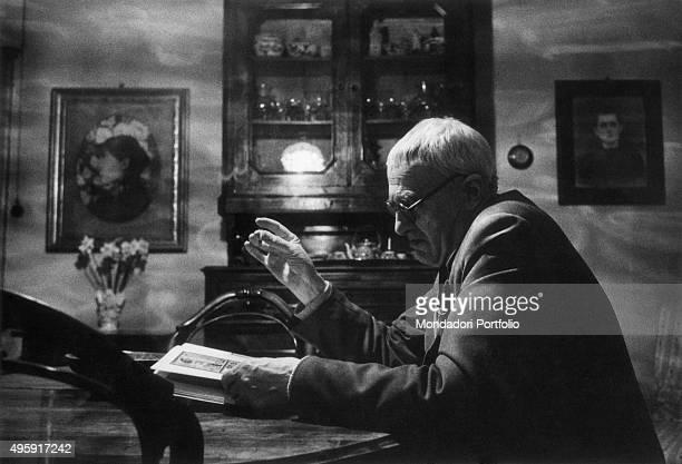 Italian painter Giorgio Morandi reading a book seated in his house on via Fondazza 36 Bologna April 1959